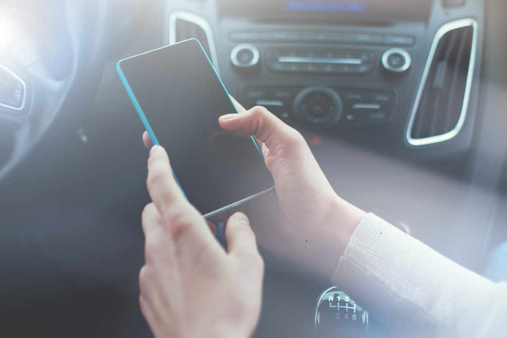Frau benutzt Smartphone im Auto